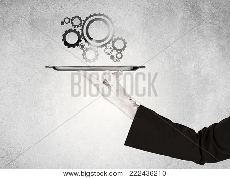 Crank wheel machine working concept with racks served on silver plate by hand in white glove and industrial grey wall pattern background.