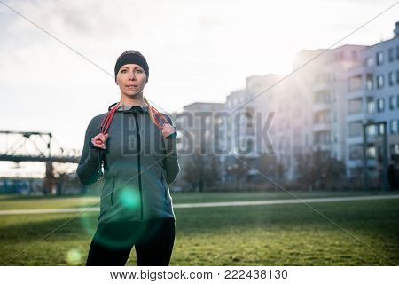 Portrait of a determined young woman daydreaming with a serious facial expression while holding a skipping rope outdoors in the park in a sunny day