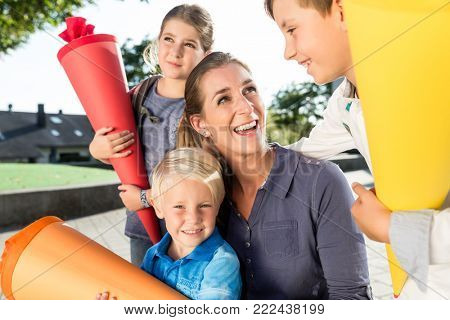 Woman and kids at enrolment day with school cones, smiling