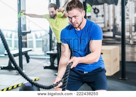 People in gym doing sport in functional fitness training with battle rope