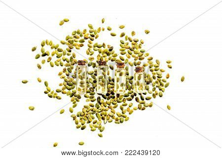 Use seed oil as cosmetics. Bottlles with pumpkin seed oil near scattered pumpkin seed on blue tablecloth on white background top view.