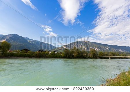 Waterfront view of Inn river along Inn promenade with big mountain, blue sky in background, in Rattenberg, Tyrol in Austria, Europe