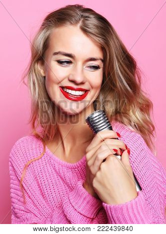 Happy singing girl. Beauty woman wearing pink pullover  with mic poster