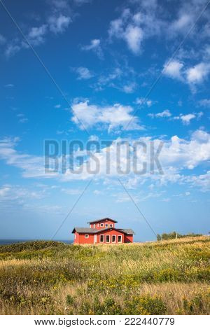 A colourful painted wooden house of Havre Aubert, with summer sky and the sea in the distance. Iles de la Madeleine, Quebec, Canada.