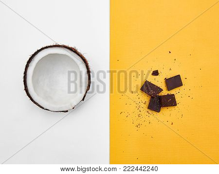 Coconut Flat lay Half coconut in peel and broken chocolate bars are lying on two-tone background Top view Trendy colorful photo mockup with space for text