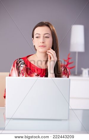 Beautiful young woman in red kimono working on laptop computer, looking away, thinking.