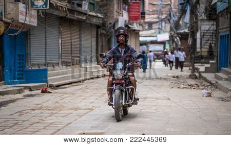 Kathmandu, Nepal - 06 October 2017: Man driving motorbike on the desolate street of Kathmandu, Nepal