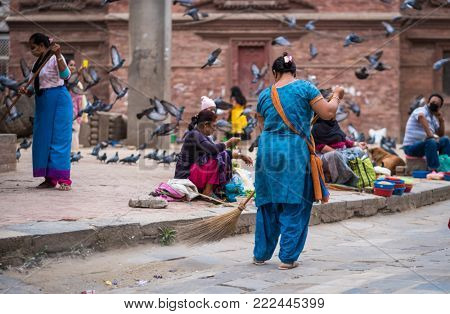 Kathmandu, Nepal - 06 October 2017: Woman in traditional blue clothes sweeping a street while other women selling on Nepalese street market
