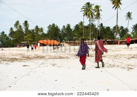 Zanzibar, Tanzania - July 09, 2016: Local people in ethnic clothes walking along beach, old boats ashore, local villages, zanzibar, tanzania