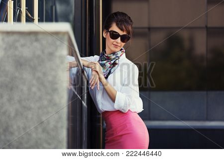 Young fashion business woman in sunglasses at office building Stylish female model in white blouse and pink pencil skirt