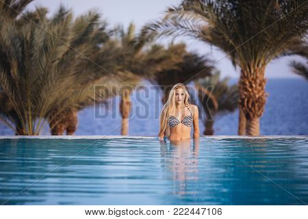 Luxury Resort. Woman Relaxing In Infinity Swimming Pool Water. Beautiful Happy Healthy Female Model