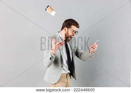 Portrait of a mad businessman dressed in suit and eyeglasses yelling at mobile phone while standing and throwing coffee cup isolated over gray background