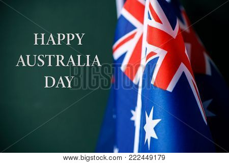 closeup of some australian flags and the text happy australia day against a dark green background