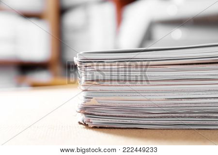Stack of old paper documents on table in archive, closeup