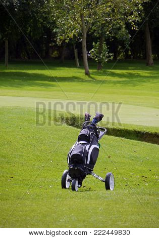 Telephoto view of lone golf trolley with golf clubs on golf course