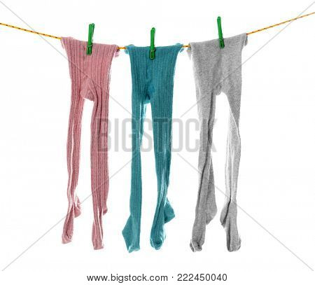 Children's tights on laundry line against white background