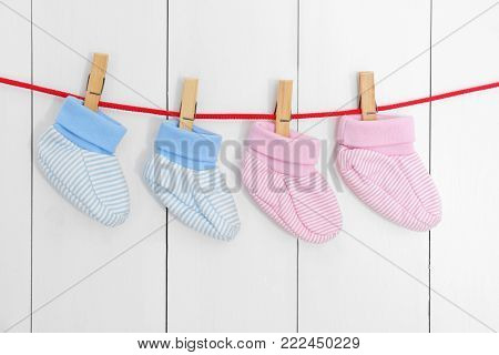 Baby booties on laundry line against wooden background