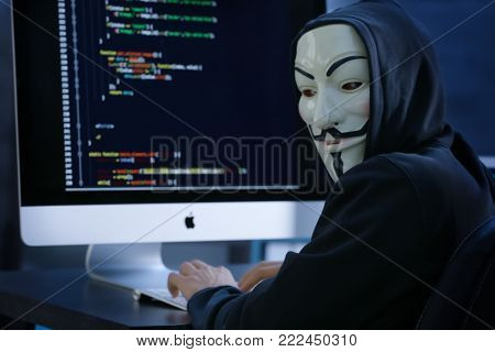 MYKOLAIV, UKRAINE - SEPTEMBER 29, 2017: Anonymous person in Guy Fawkes mask using computer indoors