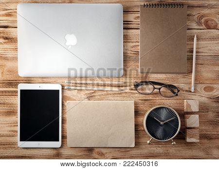 KYIV, UKRAINE - OCTOBER 24, 2017: Apple MacBook Air Silver and iPad mini 4 on wooden background