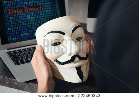MYKOLAIV, UKRAINE - SEPTEMBER 29, 2017: Man holding Guy Fawkes mask indoors