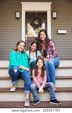 Female Multi Generation Family Sit On Steps in Front Of House