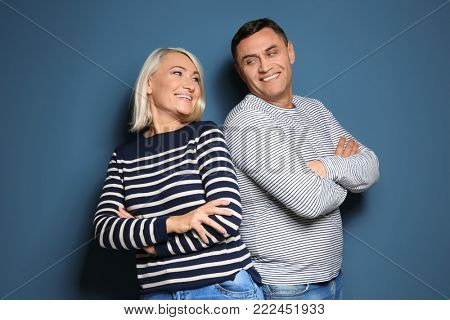 Cute middle-aged couple on color background