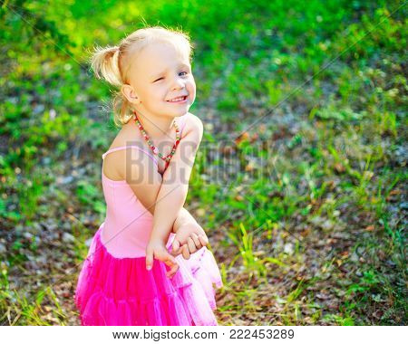 shy little girl wearing a pink dress,    in the summer park