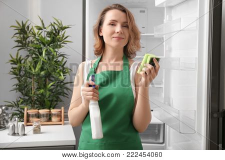 Beautiful woman with detergent and sponge standing near refrigerator in kitchen