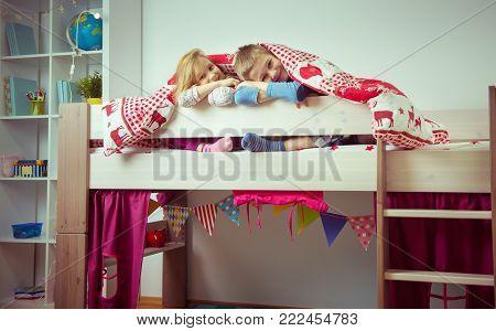 Two Happy Sibling Children Having Fun In Bunk Bed