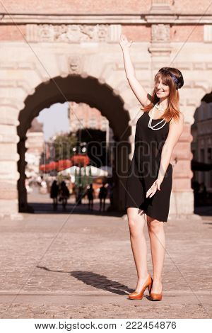 Flapper girl making inviting welcome hand gesture. Retro style fashion vintage woman in black dress outdoor on the street of old town Gdansk Danzig