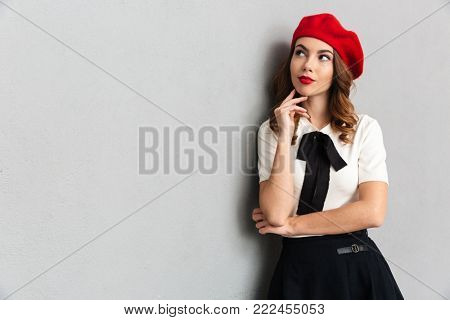 Portrait of a thoughtful schoolgirl dressed in uniform posing while standing and looking away isolated over gray wall background