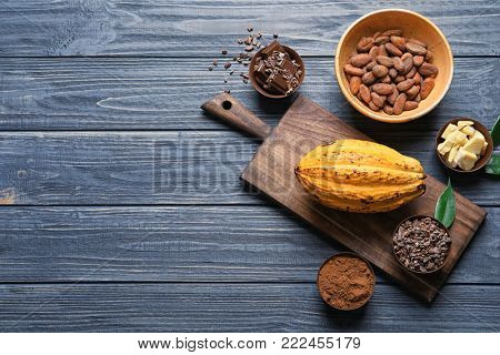 Composition with cocoa products on wooden background, top view