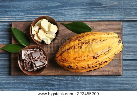Composition with cocoa pod on wooden background, top view