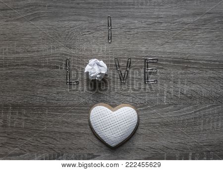 on a wooden background lies the paper clip word love instead of letter o paper lumpy crumpled cookie heart with mastic