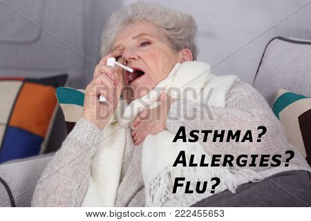 Senior woman using spray as remedy for asthma, allergies or flu at home