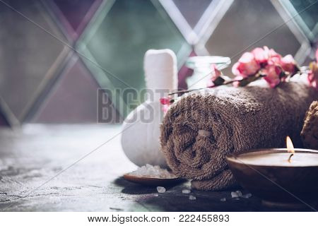 Spa concept with sea salt, massage herbal balls, candles and essencial oils on old stone background. Natural cosmetics and wellness conceptSpa. Spa treatment.