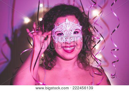 Woman wearing carnival mask at masquerade party. Close up.