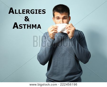 Young ill man with symptom of asthma or allergies on color background