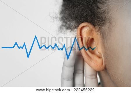 African-American girl with symptom of hearing loss on light background