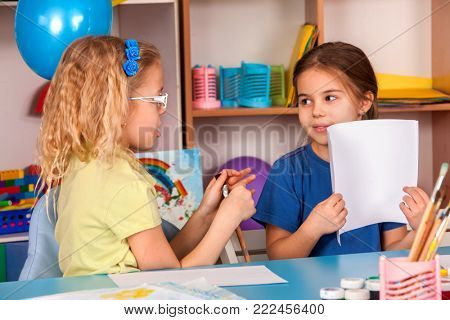 Small students painting in art school class. Child drawing by paints on table. Kid on balloons background. Top view of girl in kindergarten. Newcomer in children's team. Kids in prep school.