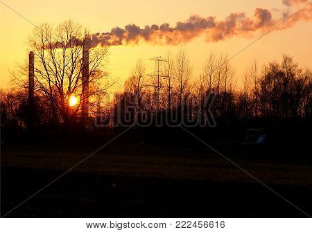Western smoke. Lodz, Poland - January 15, 2018 Smoke from the chimneys of the heat and power plant in Łódź, against the backdrop of the setting sun.