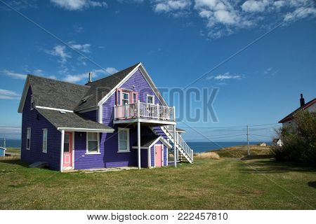 Purple house with pink windows against a blue sky in Iles de la Madeleine in Canada