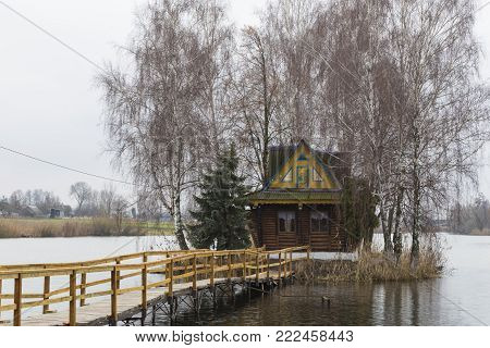 Fisherman's house with a wooden pedestrian bridge on a tiny island in the middle of the lake. Autumn view. Old  Solotvyn village. Ukraine.