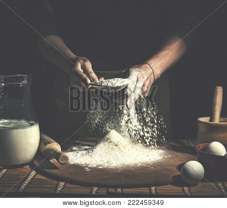 Preparation of Easter bread.Man preparing bread dough on wooden table in a bakery close up.