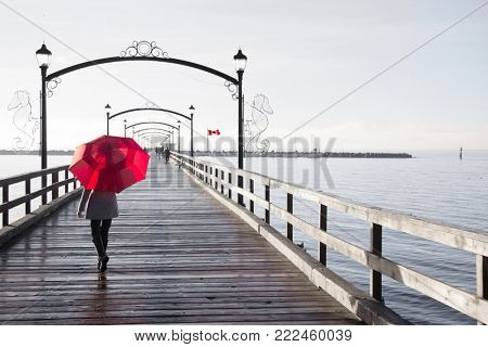 Woman holding a red umbrella walking on a rainy day on the pier in White Rock, British Columbia, Canada. A Canadian flag is visible in the background.