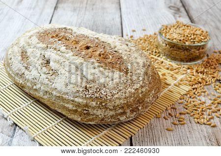 Naturally leavened spelt bread on wooden table with spelt grains