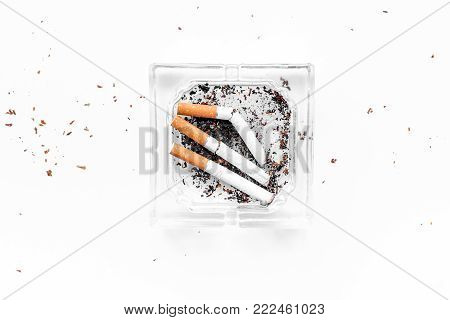Smoking. Half-smoked cigarettes in ashtray on white background top view.