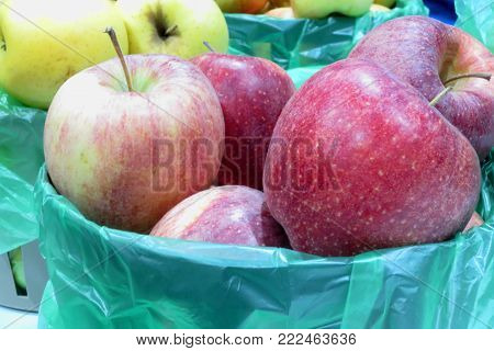 A basket of red apples with another basket full of yellow apples in the background