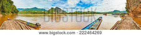 Touristic boats at the pier of Pak Ou cave. Beautiful landscape panorama, Luang Prabang, Laos.