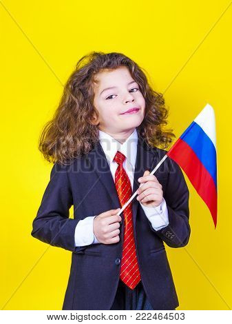 A charming boy in a business suit with a Russian flag